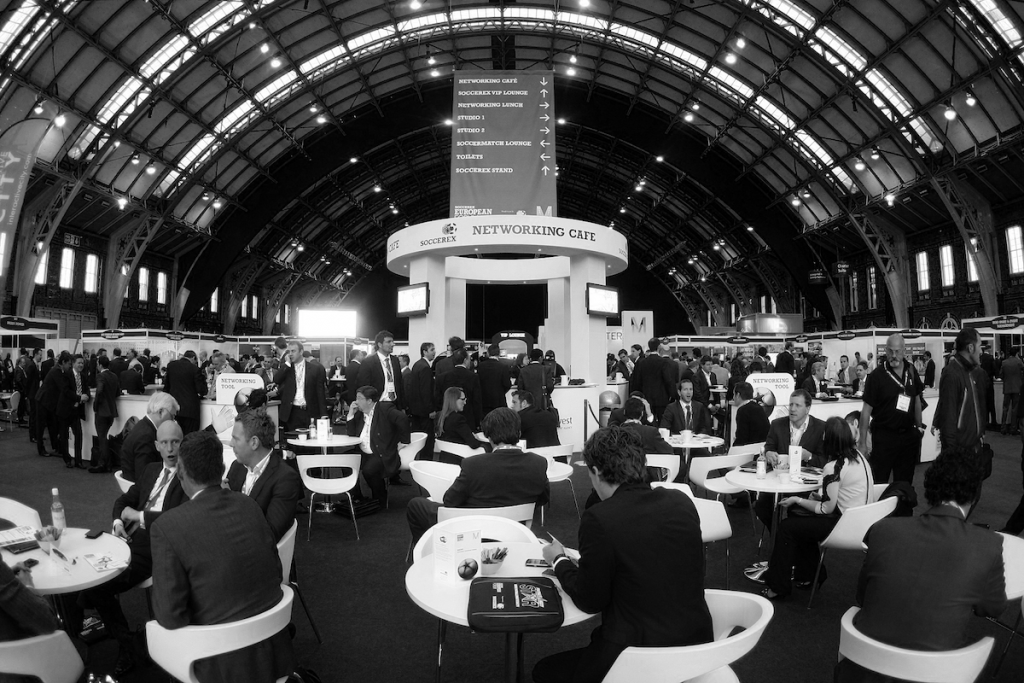 Stands, chairs, tables, people and televisions at Soccerex week